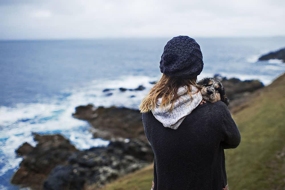 Meditation – Junge Frau mit dem Rücken zum Bild und kleinem Hund im Arm, blickt auf das Meer