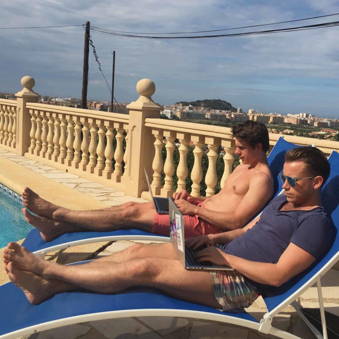 Die besten Reise-Kreditkarten – Arne und Mauricio mit MacBooks auf Liegestühlen