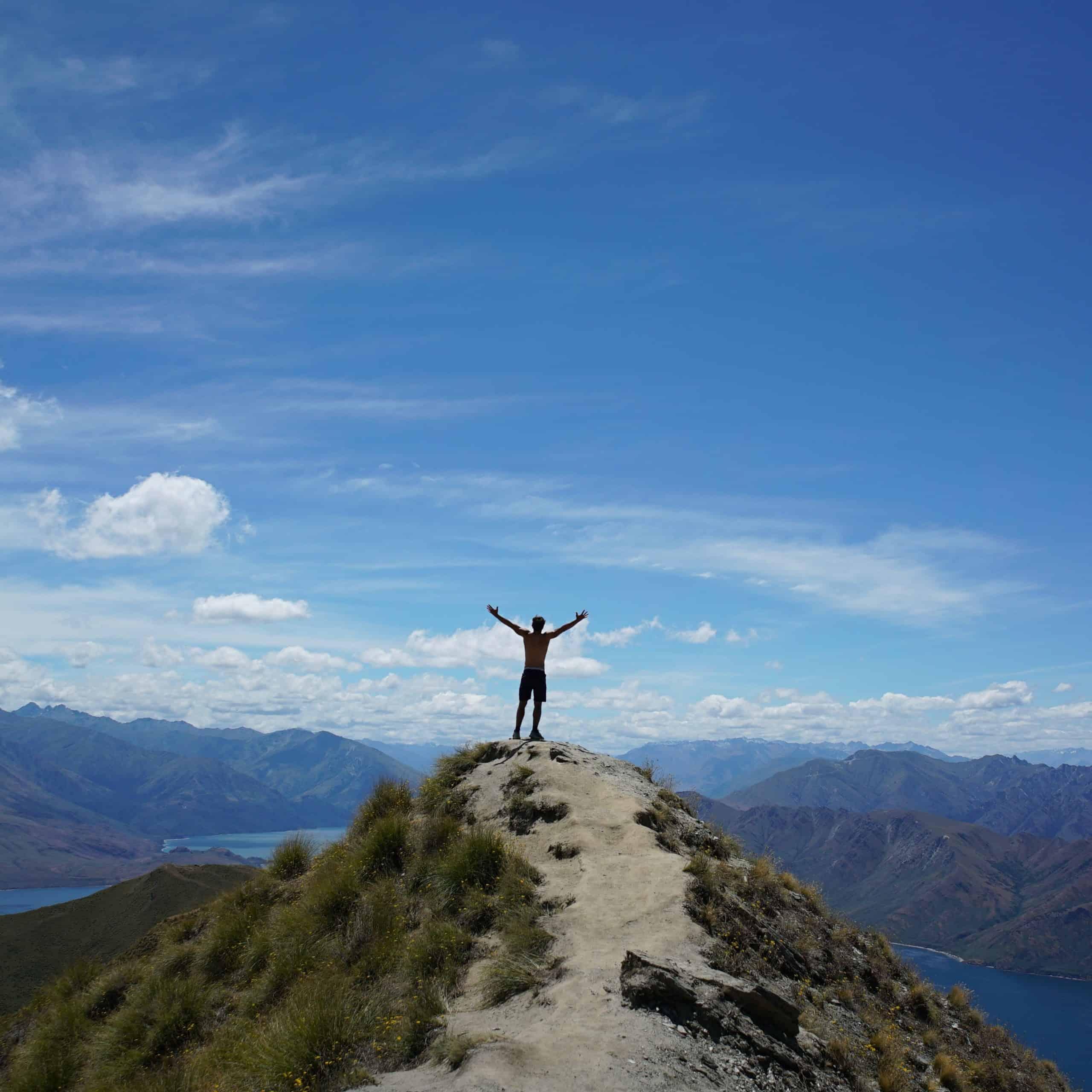 Meditation – Mauricio steht mit nach oben ausgestreckten Armen auf einem Felsen, vor ihm eine Bucht mit Gebirgsmassiv drumherum