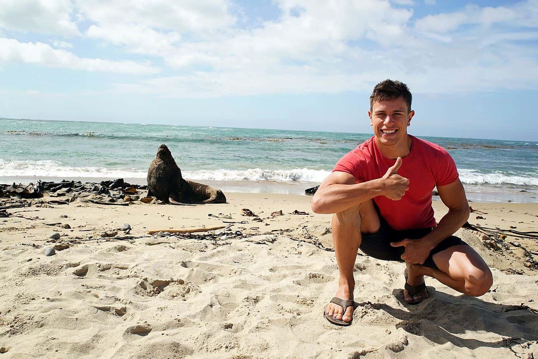 Mauricio an einem Sandstrand in Neuseeland mit einem Seelöwen im Hintergrund