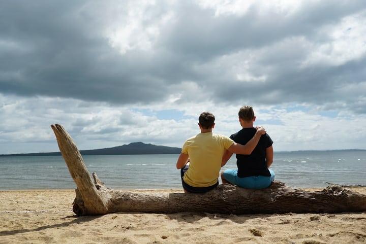 Arne und Mauri auf Baumstamm am Meer