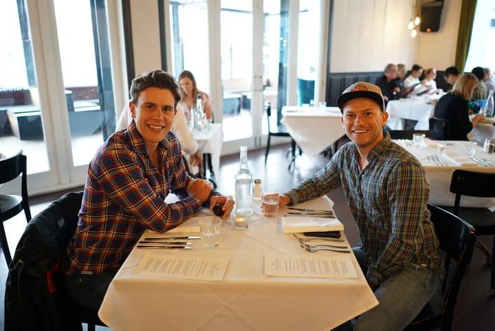 Die besten Reise-Kreditkarten – Arne und Mauricio sitzen an einem Tisch in einem Restaurant