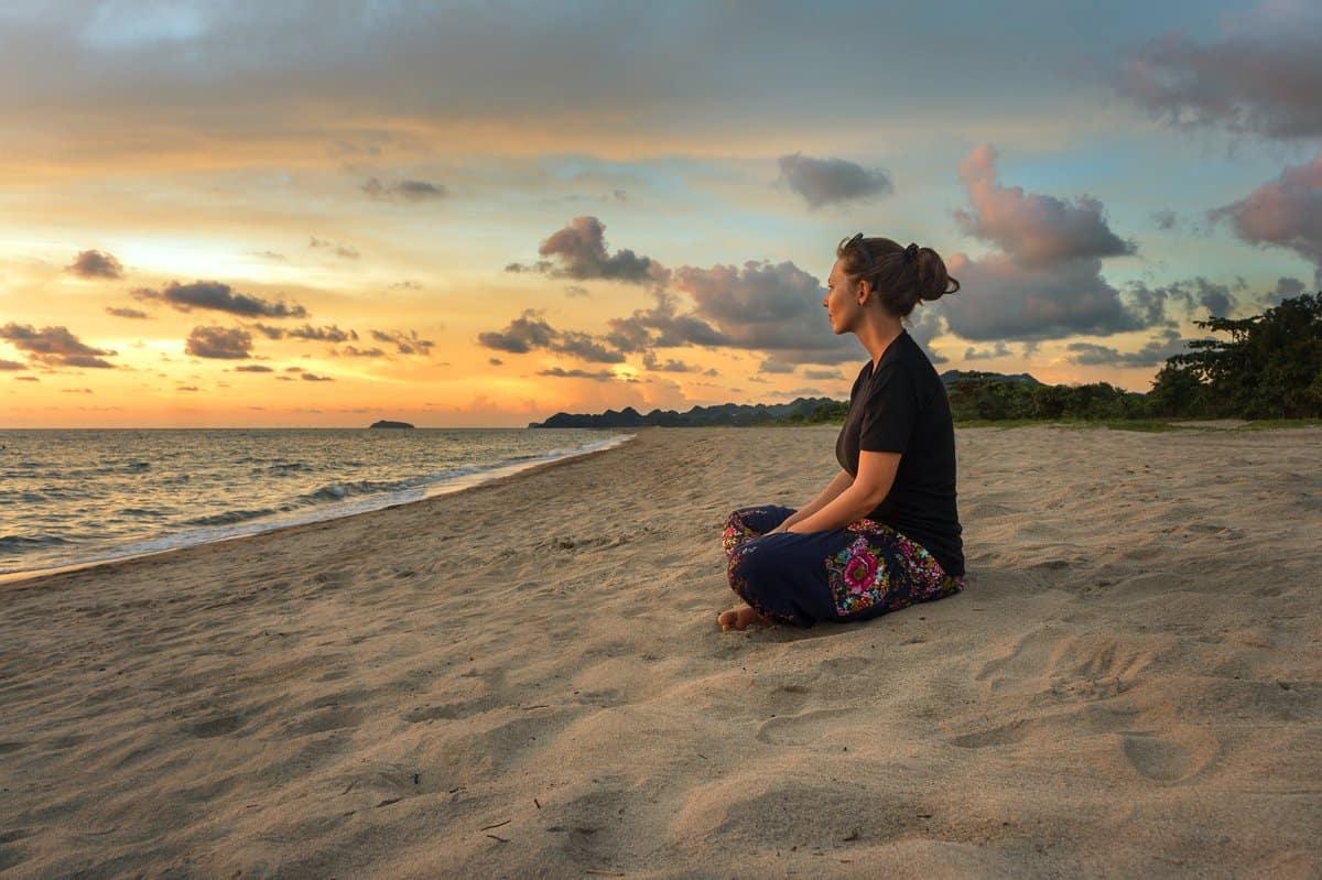 Meditation – Junge Frau sitzt in Lotuspose an einem Sandstrand, seitliche Ansicht