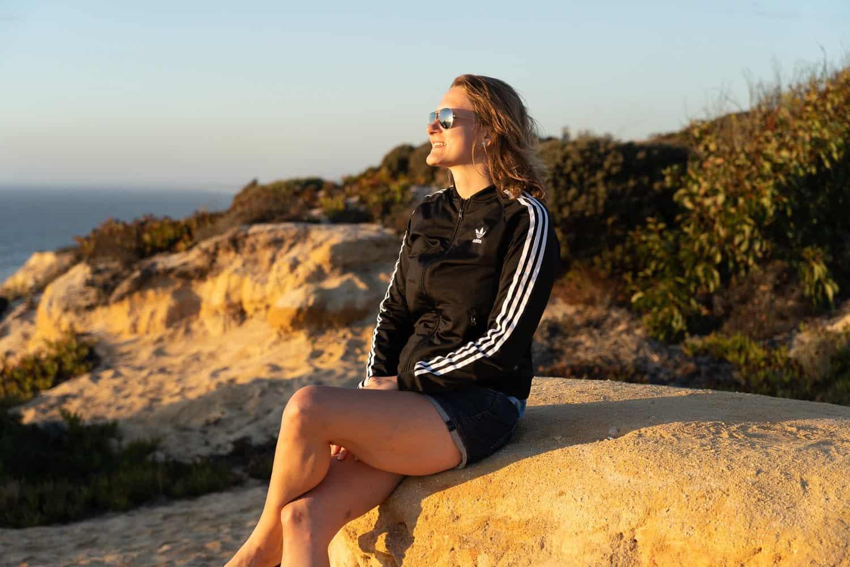 Meditation – Pauline sitzt auf einem kleinen Felsen und blickt in die untergehende Sonne