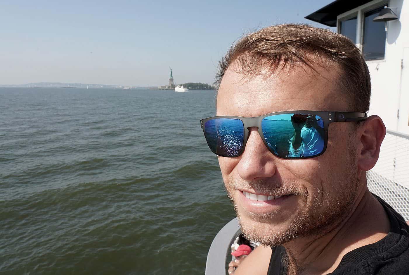 New York City – Arne bei Bootstour auf Hudson River, die Freiheitsstatue am Horizont zu sehen