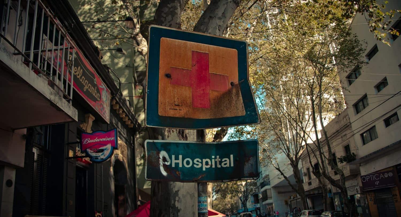 """Reisekrankenversicherung - Verbeultes Straßenschild, mit der Angabe """"Hospital"""""""