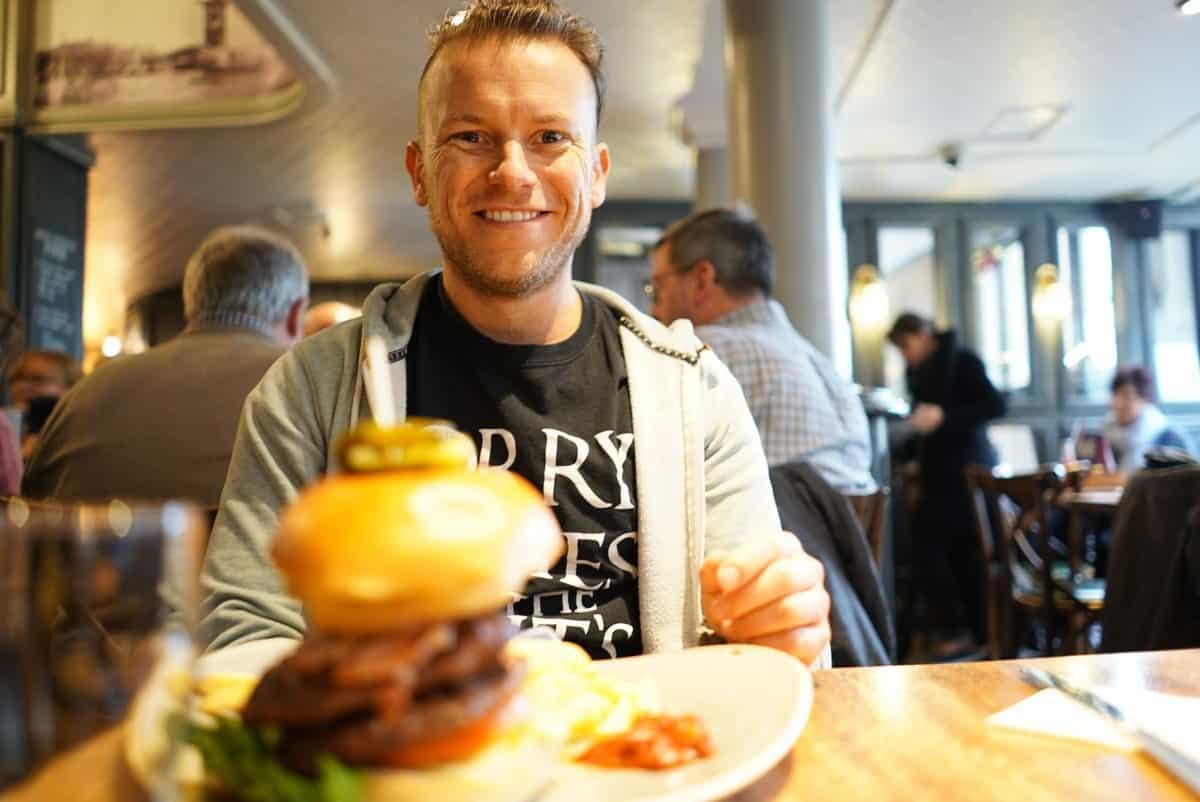 Die besten Reise-Kreditkarten – Arne lächelt in die Kamera, vor ihm ein großer Burger auf einem Teller