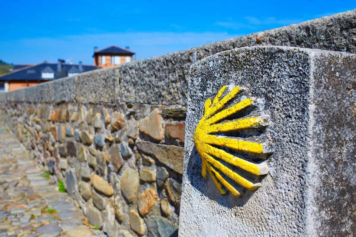 Spanien-Reise-Tipps – Steinmauer in El Bierzo mit gelber Muschel, das Zeichen für den Jakobsweg