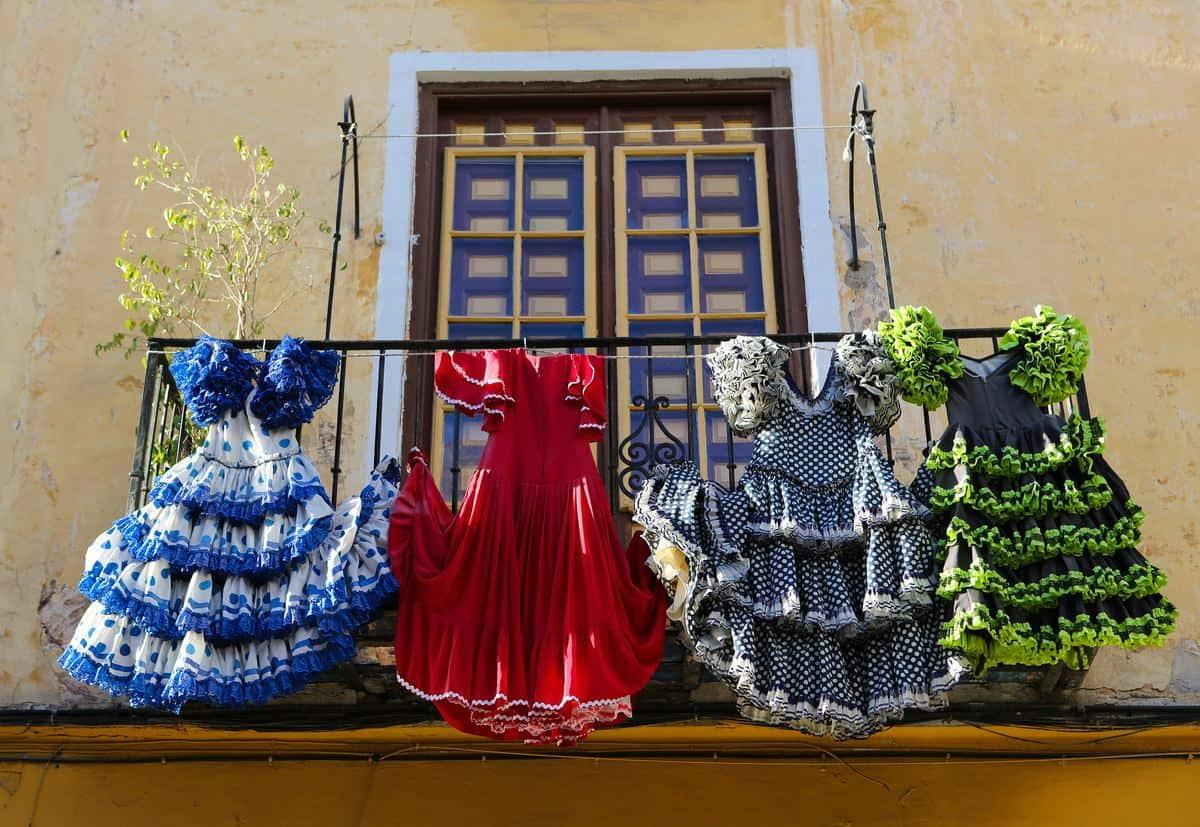 Spanien-Reise-Tipps – Balkon in Malaga, Andalusien, vor dem eine Wäscheleine gespannt ist und auf der mehrere Flamenco-Kleider hängen