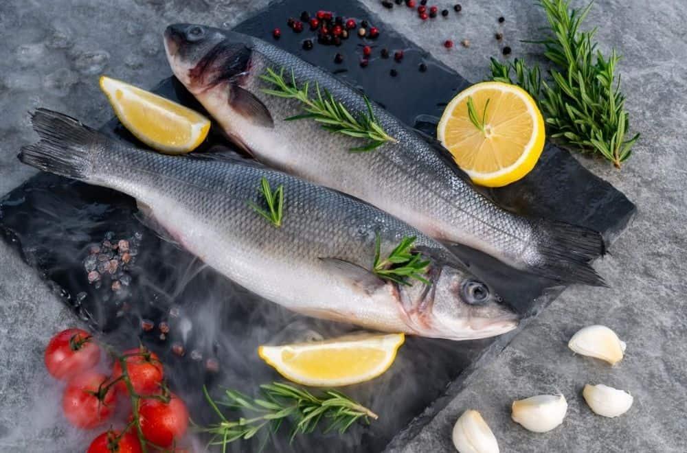 Kiel frischer roher Seebarsch mit Zitrone und Tomate