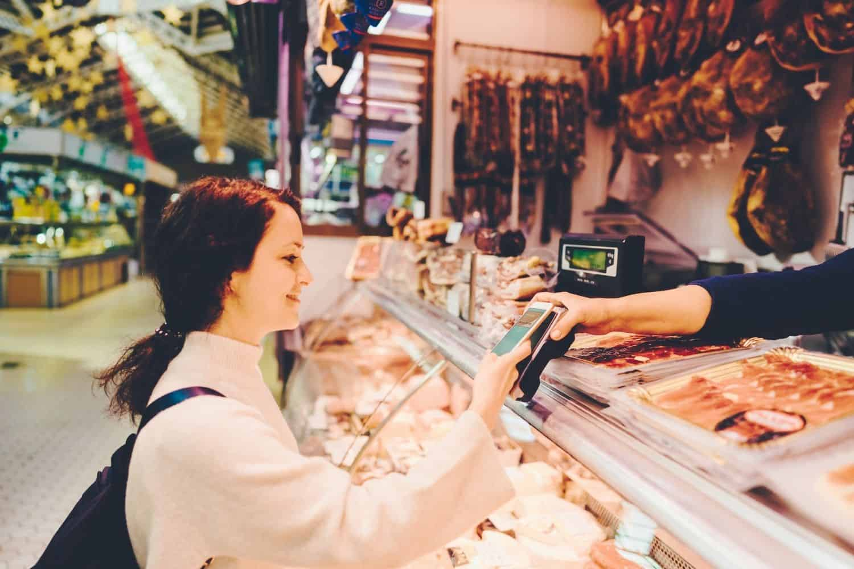 Reise Kreditkarte auf dem Markt mit dem Handy Bezahlen